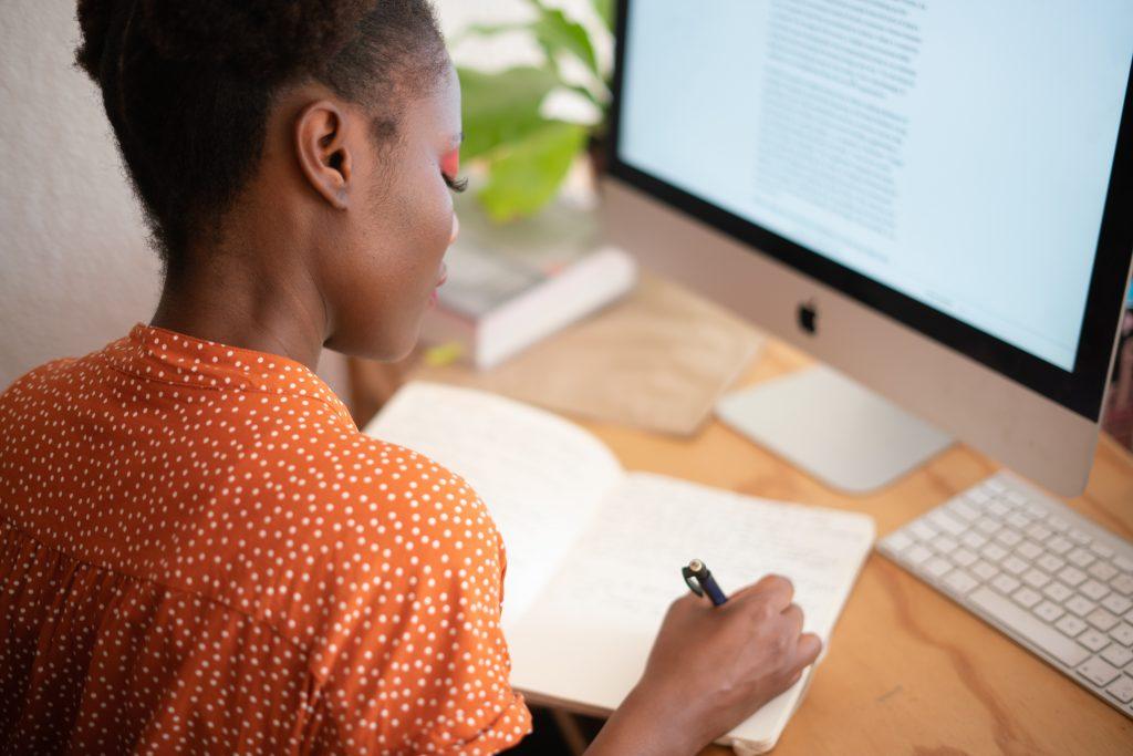 mulher negra escrevendo em seu caderno, em frente a um computador de mesa.
