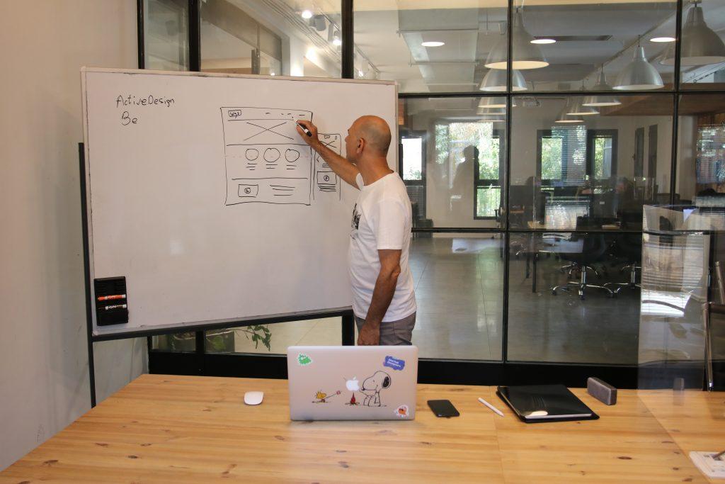 homem em frente a um quadro branco desenhando a experiencia do usuário ux writing